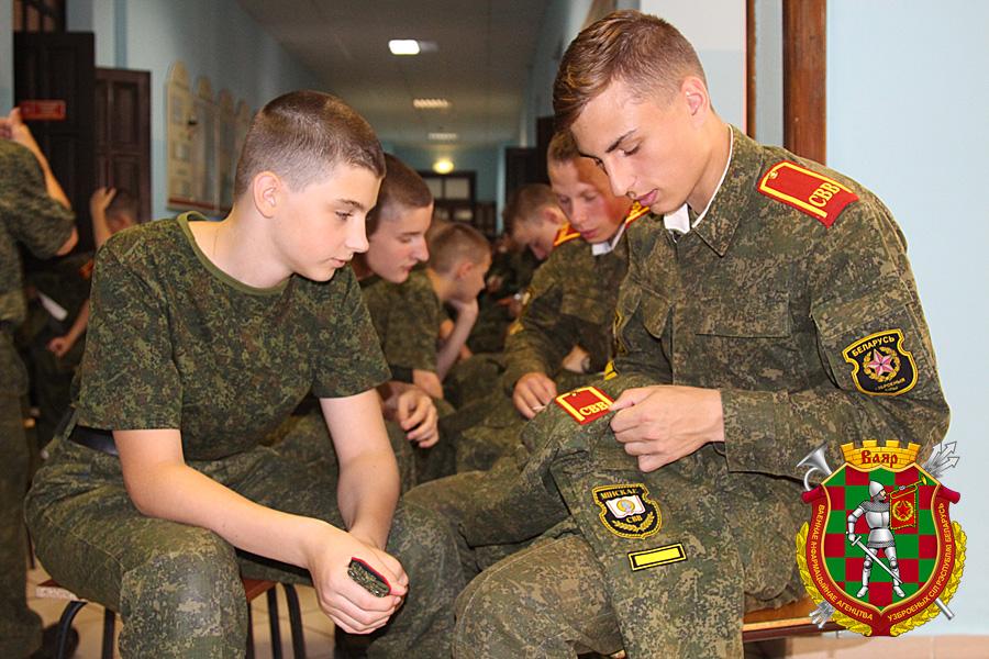 Суворовцы выпускной роты помогают младшим товарищам пришивать погоны